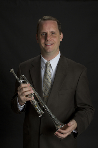 Dr. Peter Wood holding his trumpet