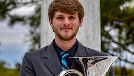 Euphoniumist Christopher Wren is picture standing with instrument in hand on the USA campus out of doors.