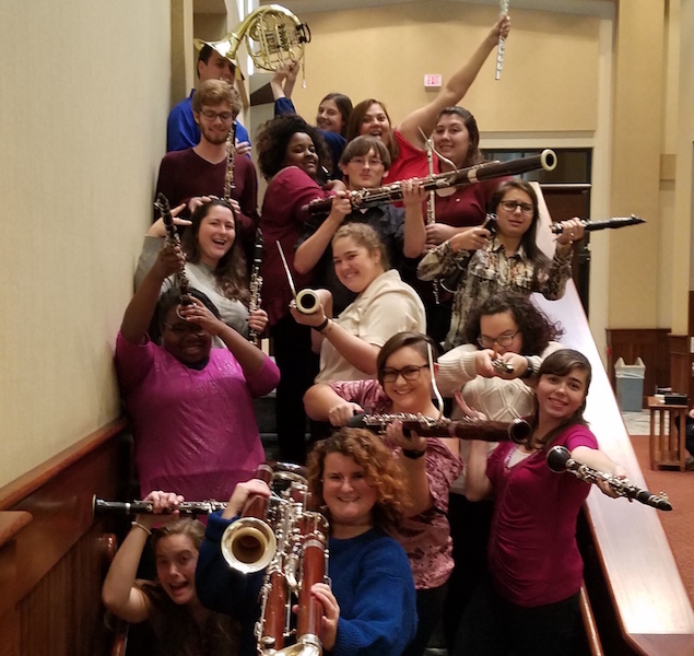 Woodwind Ensembles students posing on steps inside the Laidlaw building.