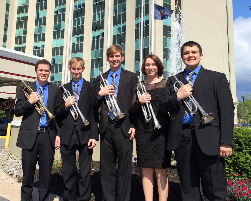 Five members of USA Trumpet Department standing outside holding their trumpets