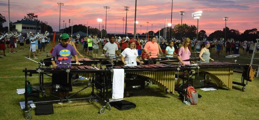 Band practicing on field at dusk,