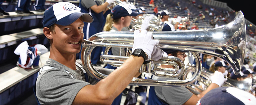Student playing trumpet in the stands