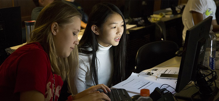 two students viewing monitor inside darkened classroom