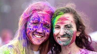 Two female students with their faces covered in color powerder from holi fest.