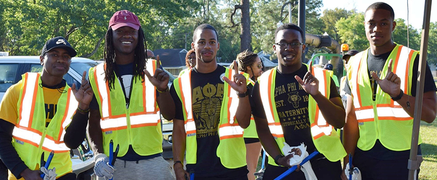 Five African American Male men in safety vests at clean up day showing J sign for Jaguars