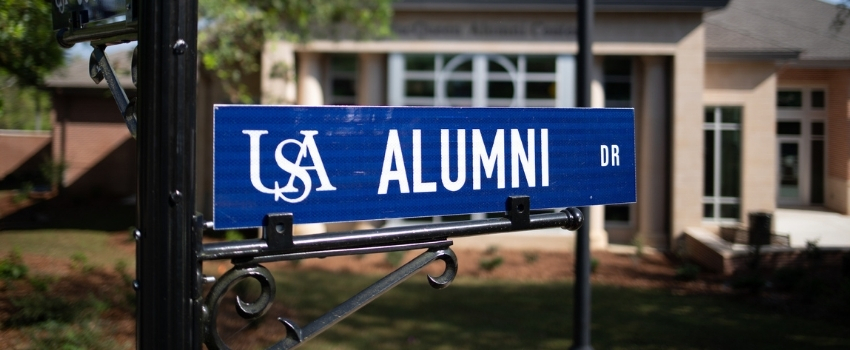 Alumni Drive street sign in front of the Alumni Center