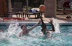 Two male students playing water basketball in Campus Rec outdoor pool.