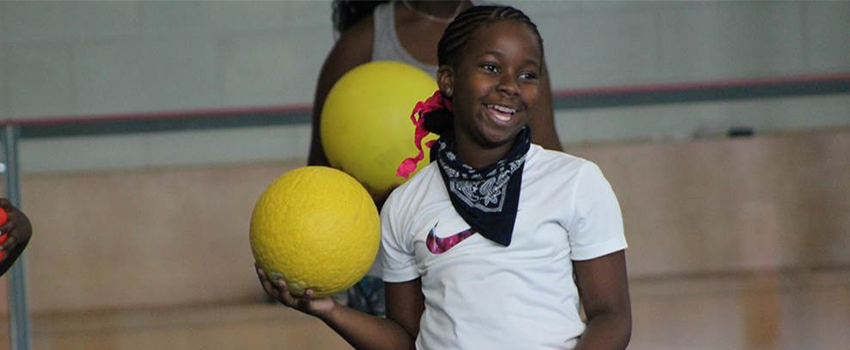 Girl holding ball in gym smiling.