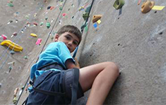 Boy climbing on rock wall.