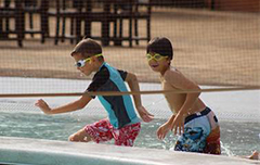 Two boys running in pool with goggles on.