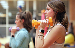 Female student lifting dumbbells