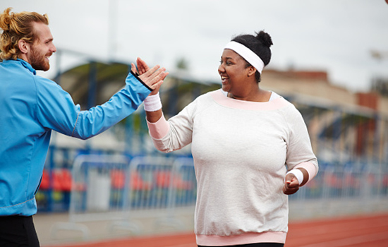 A male trainer high fiving a female on an outdoor track