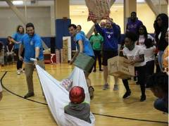 Students pulling kids on sheet in gym