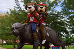 Southpaw and Miss Pawla sitting on the jaguar statue in front of the Mitchell Center.