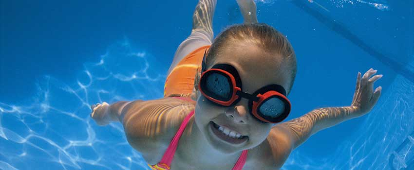 Girl in goggles and smiling swimming underwater.