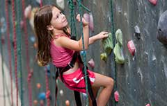 Young girl climbing on rock wall.