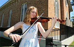 Female student playing violin outside of Bethel