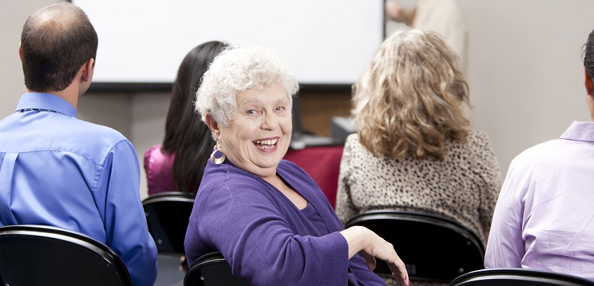 Elderly woman smiling looking over shoulder sitting in chair.