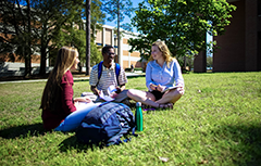 Three students sitting on grass