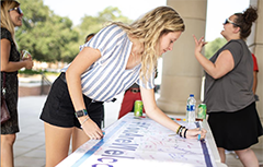 Students signing banner outside