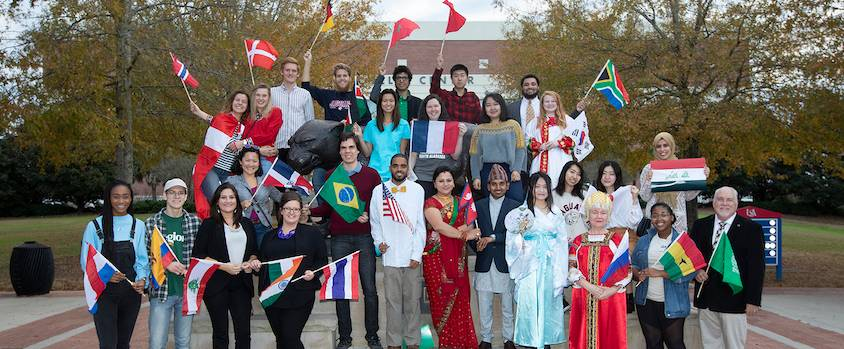 International Students in front of the Mitchell Center with flags