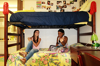 Two female students sitting on bed in dorm