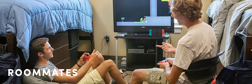 Two male students playing video games in their dorm room.