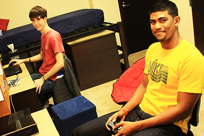 Two male students sitting in their dorm room playing video games
