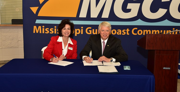 Dr. Mary Graham, Mississippi Gulf Coast Community College president, left, and Dr. Tony Waldrop, USA president, sign a commitment for the Pathway USA program.