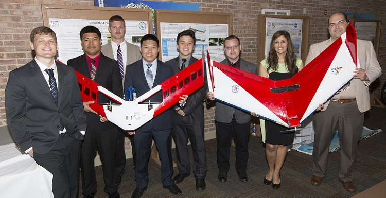 Marcus Houtzager, Lien Hoang, Caleb Cochran, Minh Lu, Michael Pham, David Sauers, Marzieh Atigh and Fariborz Bayat show off the aircraft they built for the Design/Build/Fly competition.