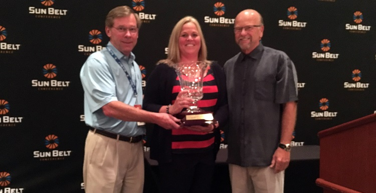 Dr. John Smith, left, USA executive vice president; Jinni Frisbey, USA associate athletic director of sports medicine and senior woman administrator; and Sun Belt Commissioner Karl Benson are pictured with the Bubas Cup, which was awarded to South Alabama for the second year in a row.