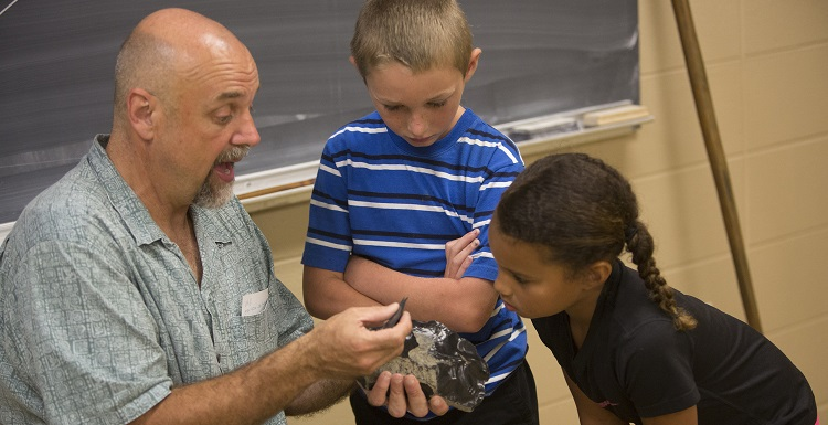 Dr. Phil Carr, Chief Calvin McGhee Endowed Professor of Native American Studies, gives a hands-on archaeology lesson to Kolby Rayborn and Kylee Langham during Art and Archaeology Day.
