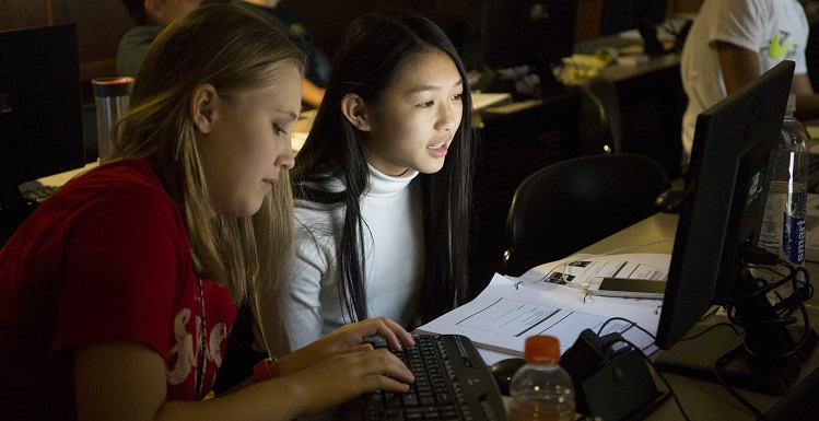 Emily Martin, left, and Tu Anh, work on encryption assignments during GenCyber Camp held at USA's School of Computing. They and other rising 9th Graders at Davidson High School participated in the week-long program. data-lightbox='featured'