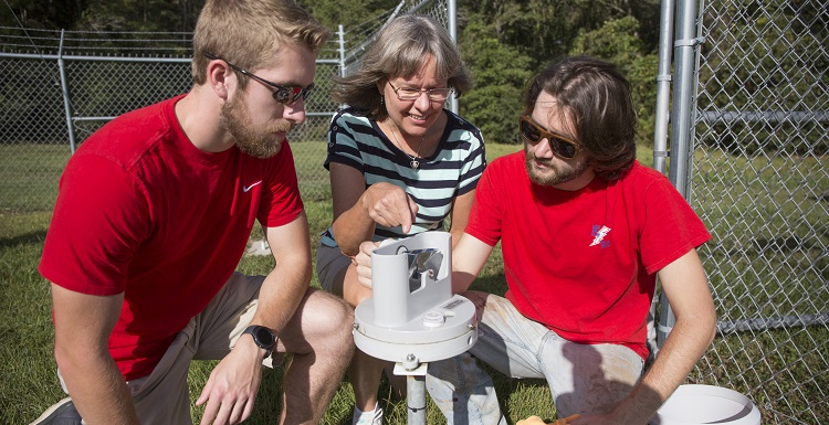 Meteorology majors Daniel Martin, left, and Mark D. Smith, right, assist Dr. Sytske Kimball, chair of earth sciences and professor of meteorology, with the USA Mesonet station on USA's main campus. Martin and Smith are both mesonet technicians.