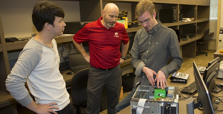 South students Thanh Nguyen, left, and Joel Dawson, right, meet with Dr. Todd Andel, associate professor of computing and principal investigator for a $4.1 million grant awarded to the School of Computing.