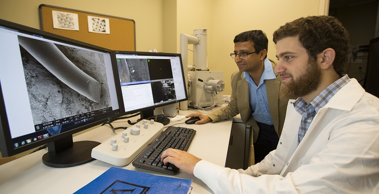 Engineering student Yousef Omar, right, and Dr. Sumit Arora, instructor in the College of Engineering's Core Facility, examine a silver wire magnified 200 times with the University's scanning electron microscope.  Silver nanoparticles are a key ingredient in their research efforts regarding sunscreens and other biomedical applications.