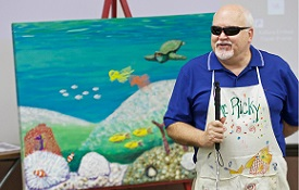 Each year, South graduate and artist Ricky Trione visits classes in the College of Education. A lesson quickly emerges: If a blind man can create boldly colored, vibrant paintings, and sit on the floor of a classroom teaching kindergarteners how to do the same, then teachers can use art to communicate with almost anyone.