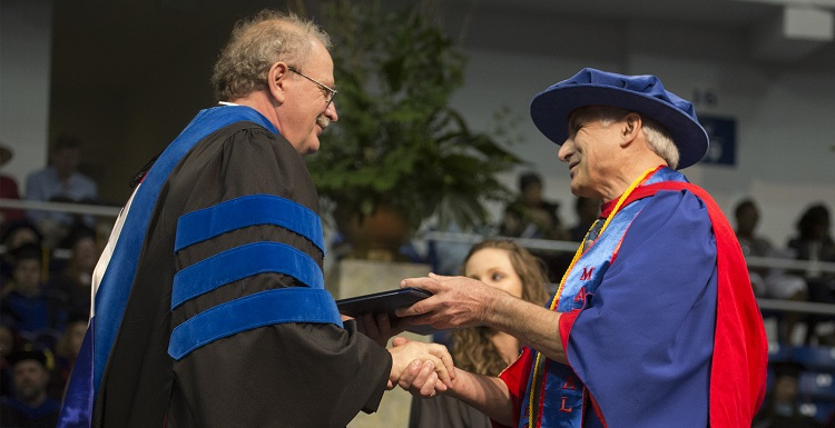 Dr. Doug Haywick, associate professor of geology, right, shakes the hand of Dr. Andrzej Wierzbicki, dean of the College of Arts and Sciences, at Commencement on May 6. Haywick earned a second bachelor's degree after taking classes beginning in 2002. data-lightbox='featured'