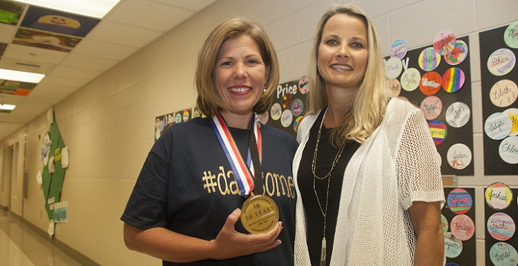 Newly-named Alabama Teacher of the Year Chasity Collier, left, receives a special 50th Anniversary medallion from Dr. Andrea Kent, dean of the University of South Alabama College of Education, during a surprise celebration pep rally at Dawes Intermediate School. Earlier this year, South Alabama's College of Education celebrated 50 years. Collier teaches fifth-grade science at Dawes Intermediate School.