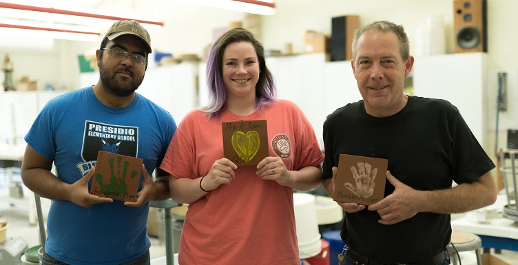 Graduate student Ramon Deanda, left, junior Lauren Carroll and Professor Tony Wright show some of the hand-print tiles that will be on display at Medal of Honor Park's playground.