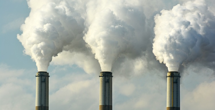 three smoke stacks with smoke billowing out