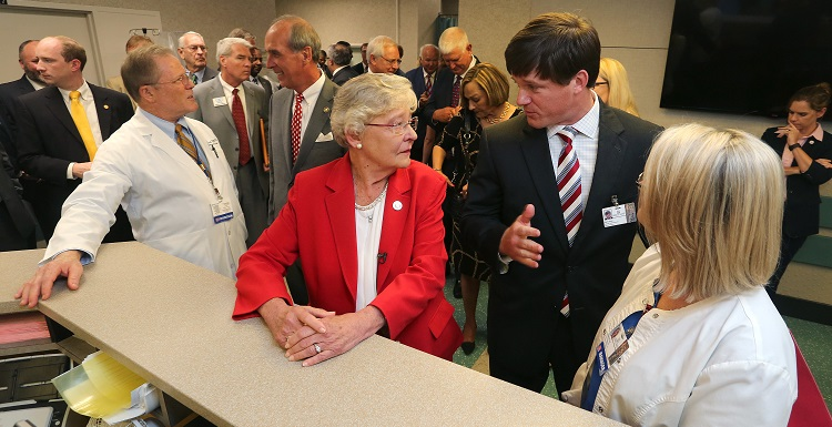 Gov. Kay Ivey, center, tours the University of South Alabama Medical Center and talks with Sam Dean, hospital administrator, before announcing a $4 million bond issue to renovate and expand the hospital's Level 1 Trauma Center.