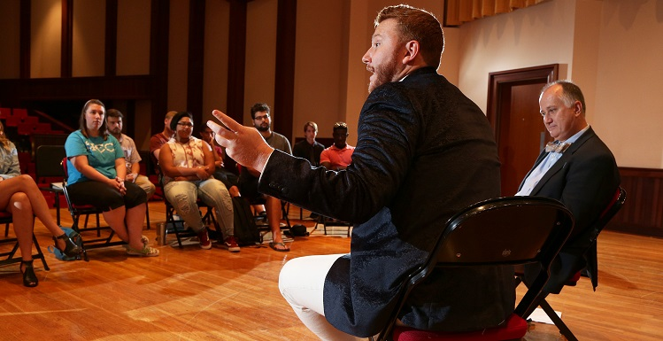 Nicholas Brownlee, front, met with music students during a visit to South, where he was taught as a student by Dr. Thomas Rowell, right, director of the USA Opera House.