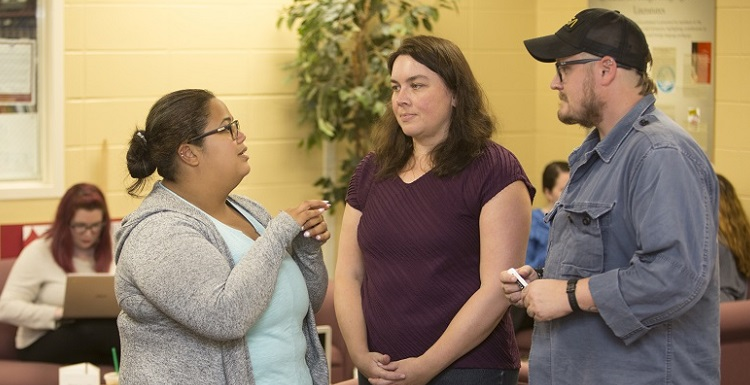Students Kassy Ureña Rodriguez, left, and Skyler Hill, right, speak with Dr. Christine Rinne, coordinator of the new Global Engagement Certificate program. Both have expressed an interest in pursuing the certificate.