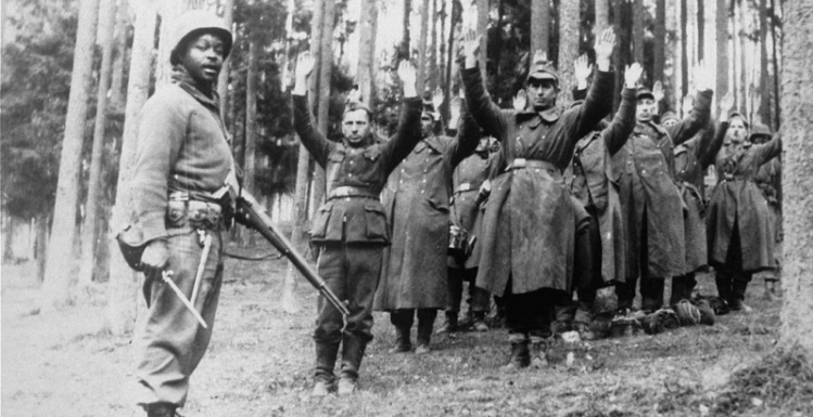 An African-American soldier with the 12th Armored Division, Seventh U.S. Army, stands guard over a group of captured German soldiers. Photo courtesy of the United States Holocaust Memorial Museum.