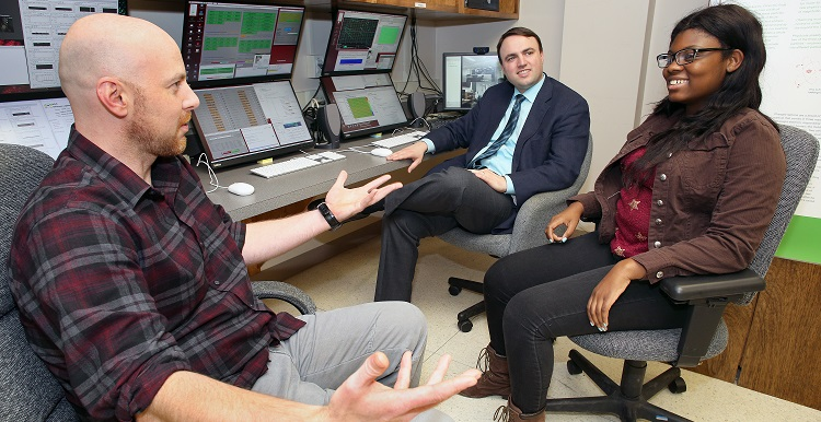 USA physics majors Paul White, left, and Erriel Milliner, right, discuss the NOvA research project with Dr. Martin Frank, assistant professor of physics, in the lab where they interact with other researchers around the country.