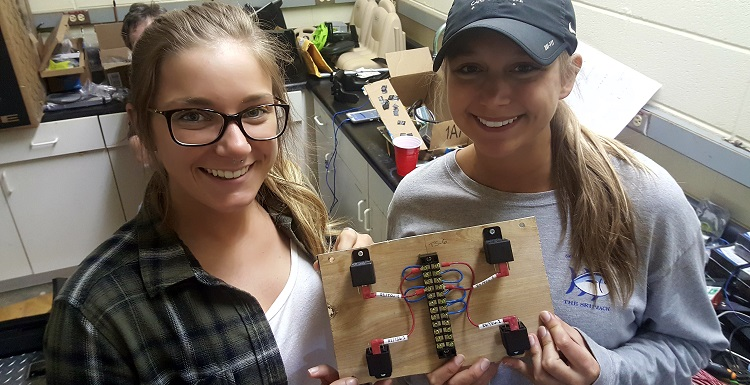 Electrical engineering students Victoria Antell, left, and Emaleigh Sargent were part of the USA Capstone Project team that modified a toy vehicle on behalf of a handicapped child. They're holding a relay board used to reverse polarity for the wheel motors, which allows for forward and reverse drive direction.