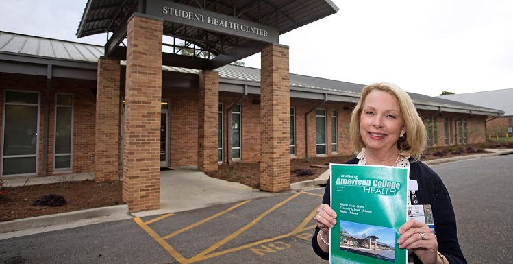 Beverly Kellen, director of operations for the USA Student Health Center, holds a recent edition of the Journal of American College Health featuring USA's Student Health Center.