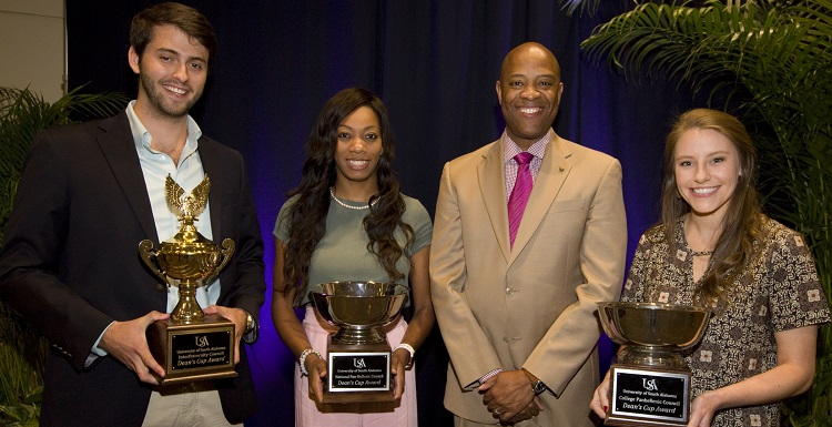 Vice President for Student Affairs and Dean of Students Dr. Michael Mitchell, right center, presents the 2018 Dean's Cup award to University of South Alabama Greek organizations for outstanding service and leadership. From left are Carson Davidenko, president of Pi Kappa Phi Fraternity; Madison Rutledge, president of Alpha Kappa Alpha Sorority, Inc.; and Brooke Qualkenbush, 2016-2017 president of Alpha Omicron Pi Fraternity.