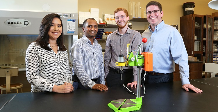 "Dr. Dhananjay Tambe, second from left, an assistant professor in mechanical engineering and pharmacology, worked with engineering students, from left, Cassandra Chapman, Brandon Stokley and Quentin Morris to develop the ""Tighten It"" smart drill prototype. Chapman and Stokely graduated Saturday."